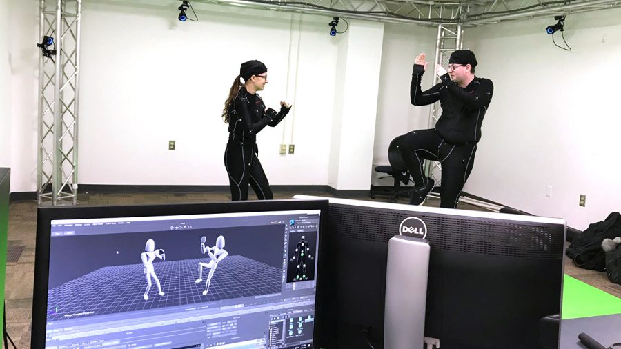 Recent graduates, Lauren McLaughlin (left) and Damian Monson (right), are seen in the Motion Capture Studio striking poses in their Mocap suits that pick up on the computer.