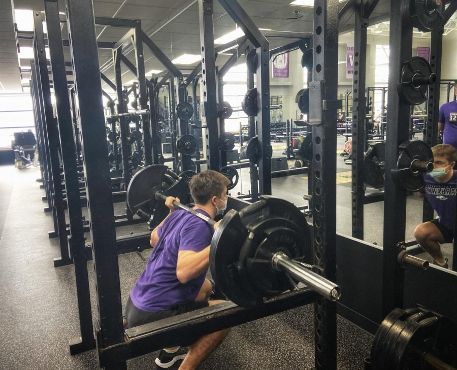 Ethan Coons and Hunter Hayberger take turns lifting weights inside the Williams Center on Thursday, Jan.14, 2021.