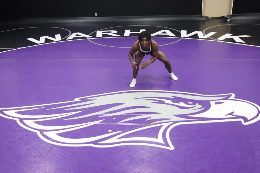 Sophomore on the University of Wisconsin-Whitewater wrestling team Dakarai Clay, holds a wrestling stance for a photo inside the Myers family wrestling gymnasium.