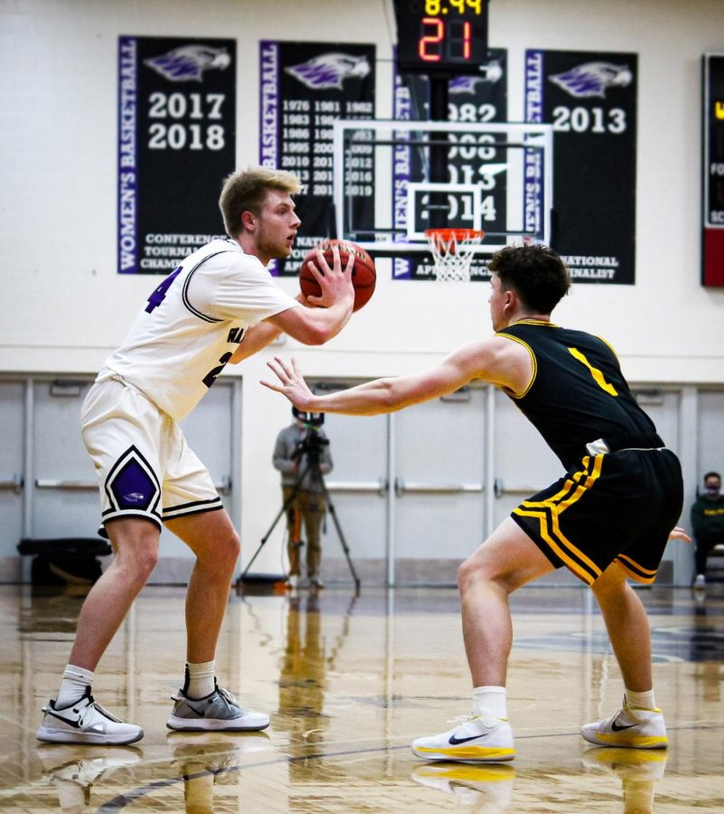 Being blocked by a UW-Oshkosh player, University of Wisconsin-Whitewater men's basketball junior forward Jack Brahm (24) looks for an opportunity to pass the ball to an open teammate.