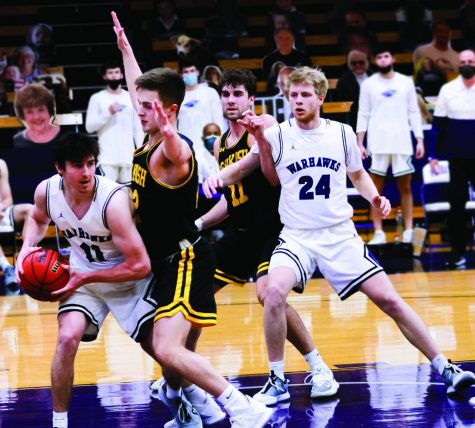 Sophomore guard Brian Conaghan (11) looks for an opportunity to pass the ball while junior forward Jack Brahm (24) blocks a UW-Oshkosh player Friday, Feb. 10.