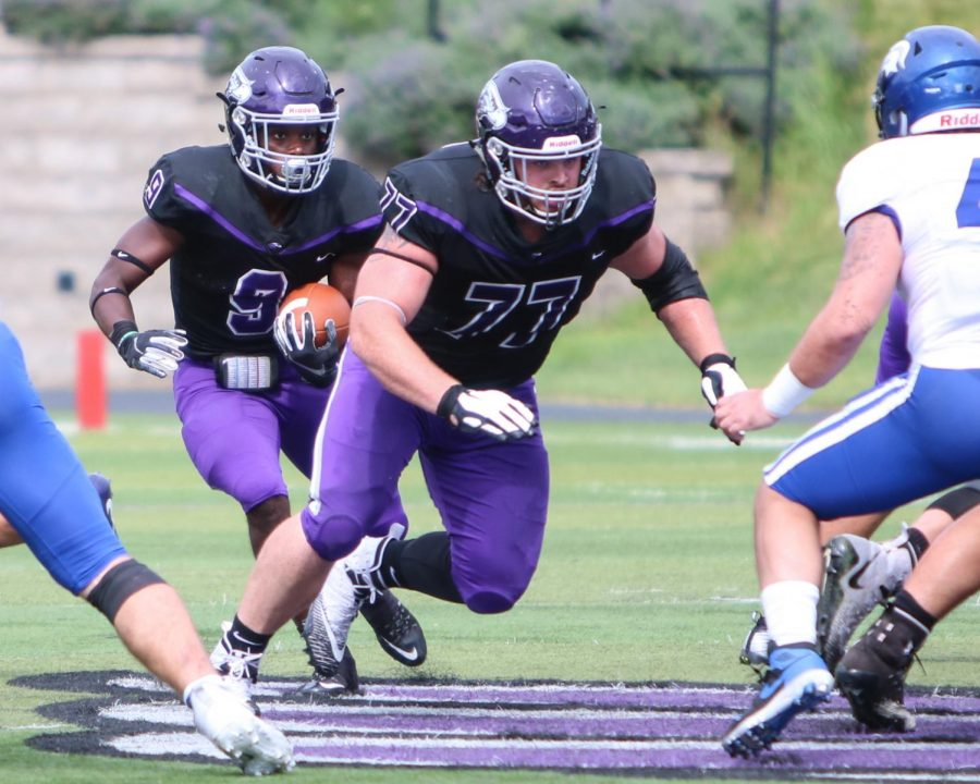 University of Wisconsin-Whitewater football offensive lineman Quinn Meinerz (77) prepares to set a block for running back Jarrod Ware (9), during a game between UW-Whitewater and Dubuque (Iowa) in September 2019.
