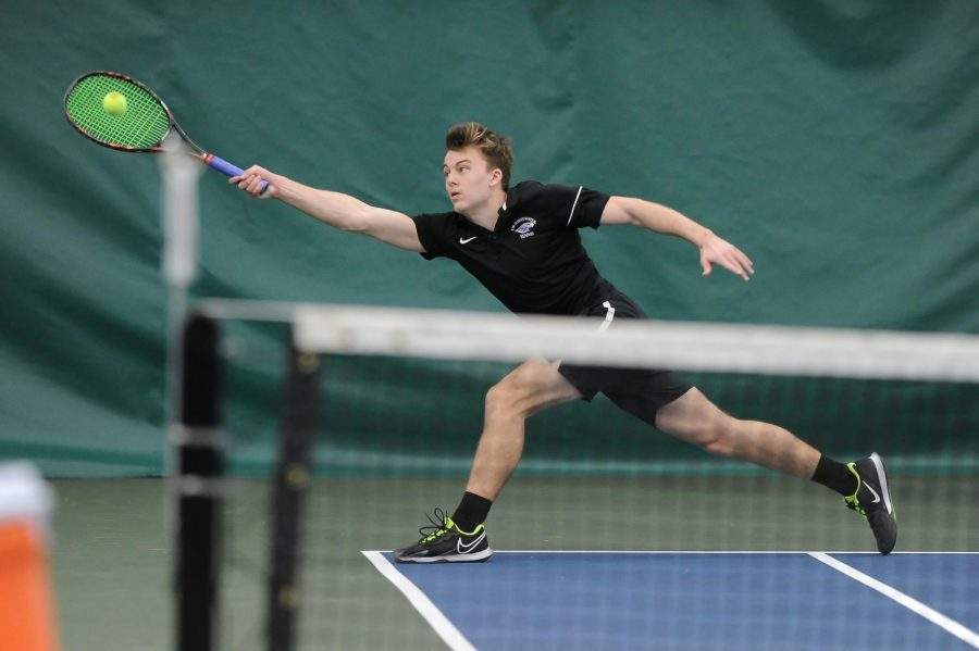 UW-W men's tennis junior Parker Hearne extends out his racket to hit the ball during the team's match against Luther (Iowa) Saturday, Feb. 13.