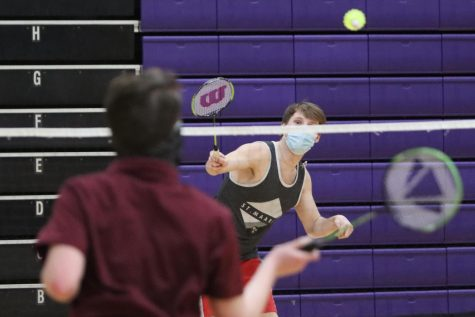 Freshman Colin Anderson watches the shuttlecock fly over the net while competing in the badminton club doubles tournament final, Tuesday March 16.