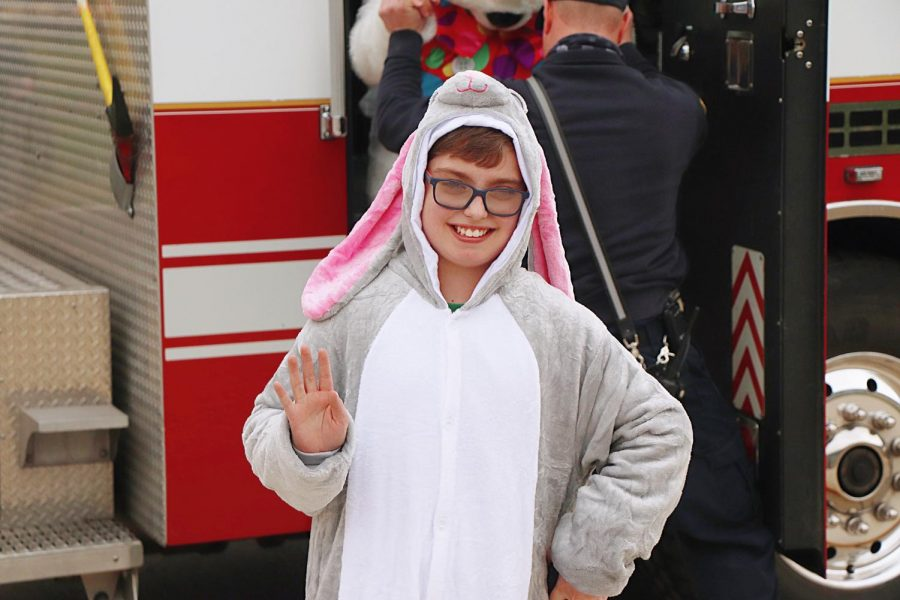 Volunteer Jack Hartmann waves near a firetruck escorting the Easter drive-thru at Whitewater Middle School Saturday, March 27.