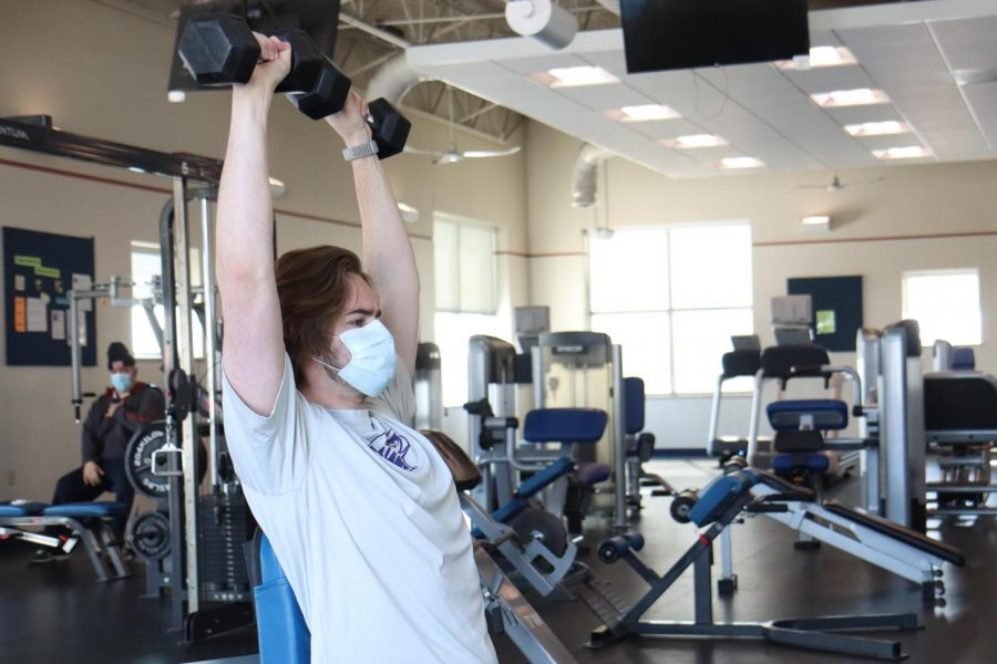 Bennett Andrews uses a pair dumbbells while working out inside the Whitewater Aquatic & Fitness Center Friday Feb. 19.