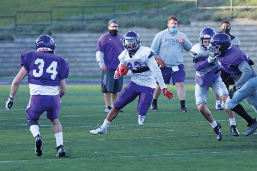 Senior running back Alex Peete (23) makes a move on a defender while running the ball, during a morning practice in November 2020 at Perkins Stadium.