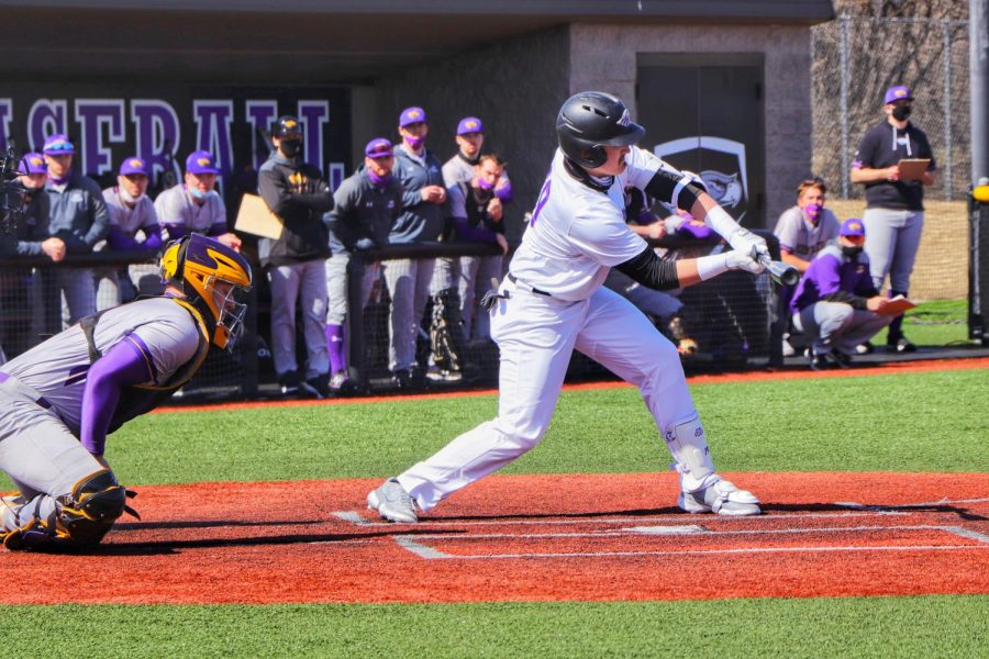 Sophomore Outfielder Matt Korman (19) attempts to hit the baseball during the Warhawks home opener. The team played a doubleheader against UW-Stevens Point winning both games.