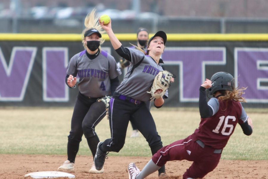 Freshman+shortstop+and+outfielder+Meghan+Dunning+%28Center%29+throws+the+softball+towards+first+base+while+University+of+Chicago+sophomore+Lola+Fisher+%2816%29+attempts+to+slide+into+second+base.+The+Warhawks+played+The+University+of+Chicago+in+a+doubleheader+Saturday+March+27.+