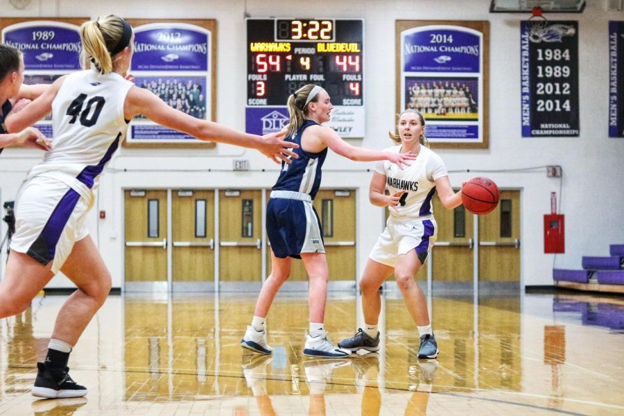 Senior guard Rebekah Schumacher (14) (right) looks to pass the ball to center Johanna Taylor (40) during the Warhawks' first round game against the Blue Devils.