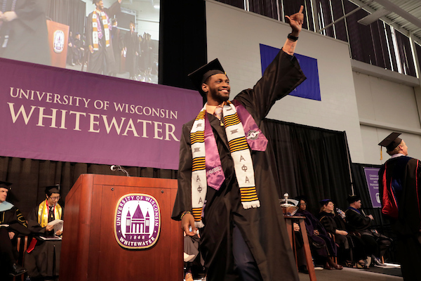 Leonard Brox, a liberal studies graduate from Milwaukee, salutes the crowd as he crosses the stage at UW-Whitewater's commencement Saturday, May 18, 2019, in Kachel Fieldhouse. (UW-Whitewater photo/Andy Manis)