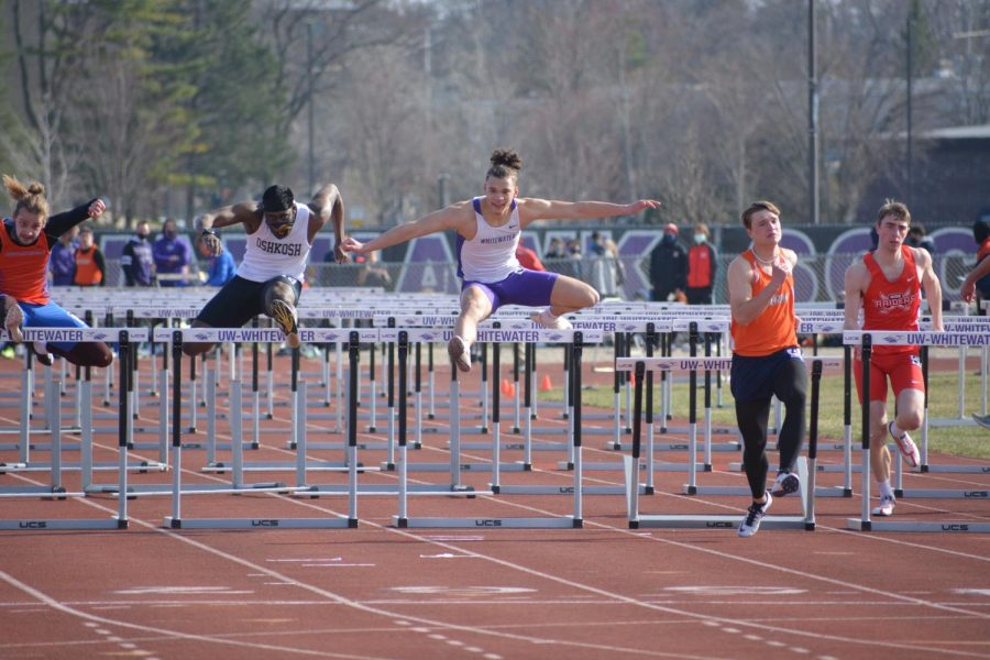 Freshman Marlon Cystrunk (Center) leaps over a hurdle while competing for the Warhawks during the Rex Foster Twilight meet.