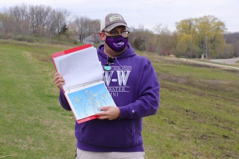 Sustainability Director Wesley Enterline flips through a binder of Wisconsin vegetation wildlife and talks about which flowers will be sprouting on the University of Wisconsin Whitewater campus this summer, Thursday, April 15.