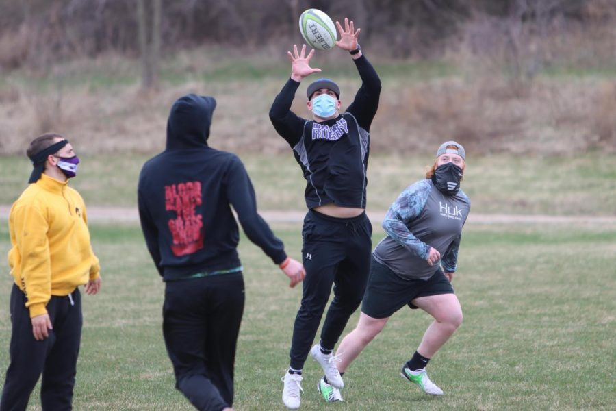Myles Schumaker (center right) leaps up to catch the rugby ball during a UW-Whitewater men's rugby club practice Wednesday March 31.