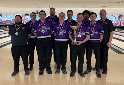 The UW-Whitewater men's bowling club team stands for a photo with the trophy after winning the 2021 collegiate club bowling national championship for the second consecutive year.