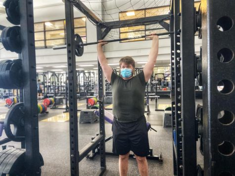 Tyler Wiley forcefully raises his arms while lifting weights inside the Williams Center.