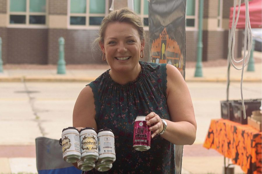 Mary Cottle happily holds up the beers in her tent at the Whitewater city market, Tuesday evening, August 24th.