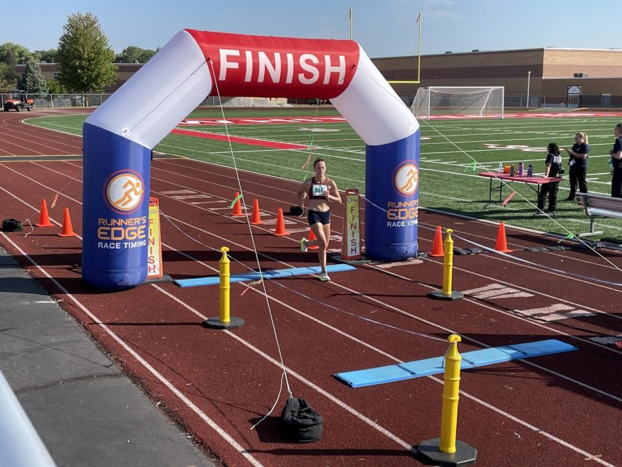 A runner runs through the finish line giving it all they got.