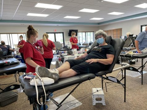 Eda Wilson, a community member donating blood with a fellow Red Cross nurse.