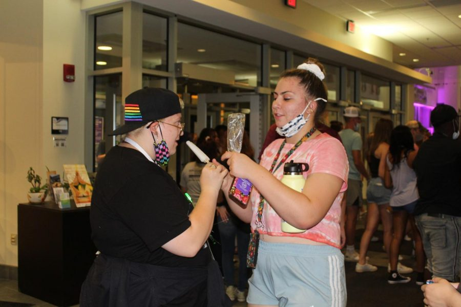 Freshman Orin Smith and Nadia Wolowik are seen sharing a popsicle during Glow Night at the University Center Aug. 30.