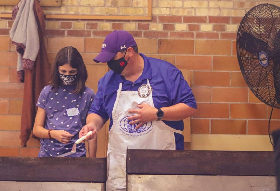 Professor Corey Davis of the Communication Department shows daughter Maya Davis how to flip a pancake at his station in the Whitewater Armory Saturday, Sept. 25, 2021.
