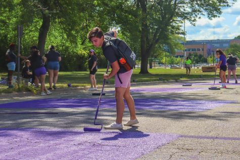 Peer mentor Hunter Nobles paints Warhawk Drive Sept. 1. Paint it Purple is an annual University of Wisconsin-Whitewater tradition for incoming freshmen as they begin their college journey.