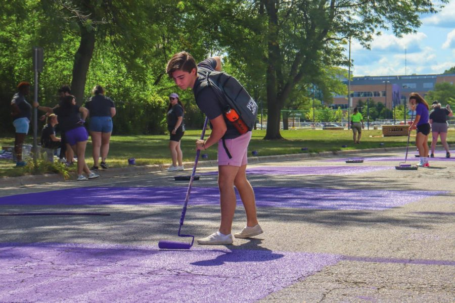 Peer+mentor+Hunter+Nobles+paints+Warhawk+Drive+Sept.+1.+Paint+it+Purple+is+an+annual+University+of+Wisconsin-Whitewater+tradition+for+incoming+freshmen+as+they+begin+their+college+journey.