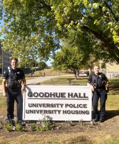 Residence Hall Officers Dan Kuehl, as he stands on the left and Alison Fish, as she stands on the right, pose for a photo outside of the University Police headquarters.