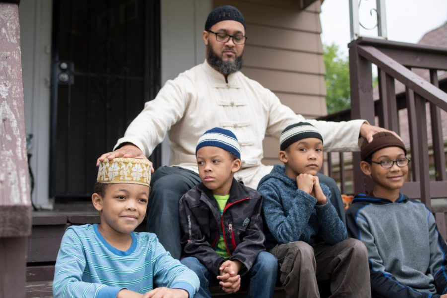 Nazir Al-Mujaahid, top, and his sons, from bottom left: Shu'aib, 9, Sayfullah, 3, Suraqah, 6, and Naser, 10, are seen outside of their Milwaukee rental home on July 8, 2021. Shu'aib and Sayfullah have tested positive for high levels of lead, a neurotoxin that damages the brain and nervous system, particularly in young children. The family suspects the lead pipe that carries water into their home is to blame.