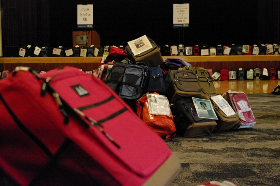 Backpacks organized in piles and lines in the Hamilton Room of the James R. Connor University Center, most with descriptions explaining the lives of those who claimed their own, Oct. 5, 2021.