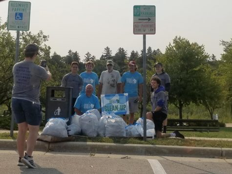 Volunteers posing in front of trash picked up from park and lake